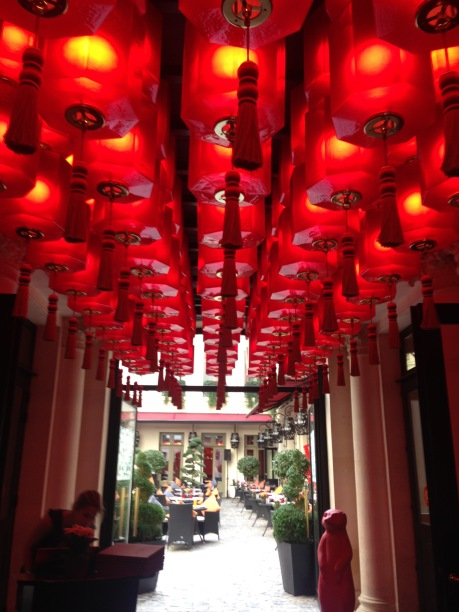 The red glow of lanterns welcome you to the hotel with a view of the courtyard.